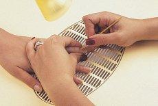 Отодвигают  кутикулу на ногте с помощью специальной лопаточки,для того, чтобы ровнее положить смолу.
